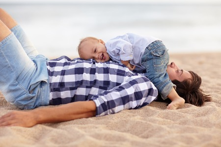 Photo pour Cute little baby boy lying on his dad's chest and laughing out loud at the beach - image libre de droit