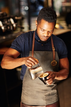 Foto für High angle view of a handsome African man carefully pouring frothy milk from a stainless steel jug into a cappucino, in the coffee shop where he works as a barista - Lizenzfreies Bild