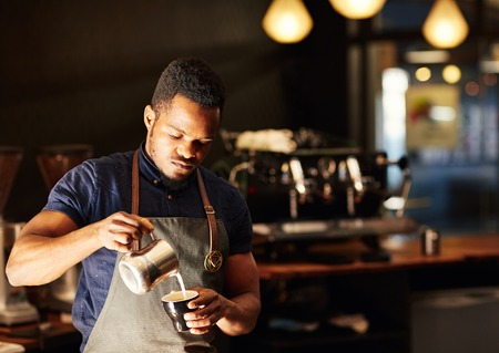 Photo pour Handsome African man pouring frothed milk carefully into a cappucino, with a gentle morning light and a modern coffee shop behind him where he has a job as a barista - image libre de droit