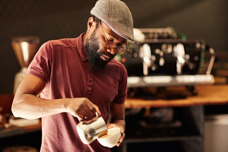 Photo pour Handsome African barista with spectacles and a stylish cap, pouring milk into a cappucino in a modern coffee shop - image libre de droit