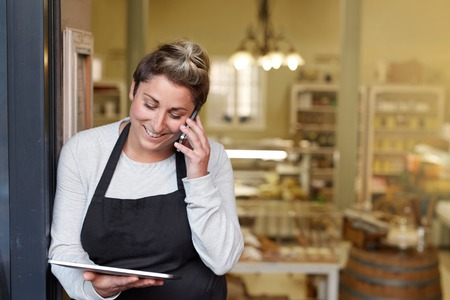 Photo pour A young deli employee talking on the phone while working on a tablet - image libre de droit