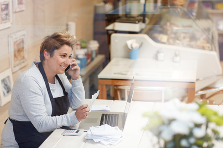 Photo for A female deli owner doing her taxes in her shop - Royalty Free Image