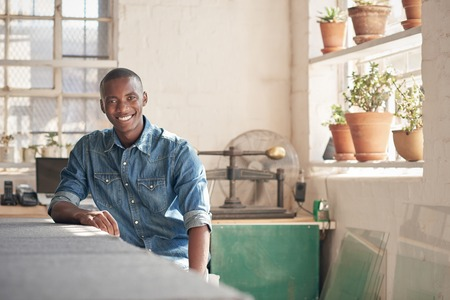Photo pour Young man of African descent sitting at his designer work bench and smiling comfortably at the camera, with soft light through the windows of his workshop - image libre de droit