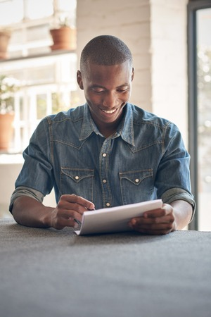 Photo pour Handsome young man of African descent sitting in a beautifully lit space smiling while filling in some paperwork - image libre de droit