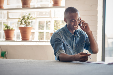 Photo pour Young African man with a handsome smile, talking happily on his mobile phone while sitting in a beautifully lit designer studio - image libre de droit