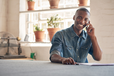 Photo pour Potrait of a handsome young man of African descent sitting in his beautifully lit design studio, talking on his mobile phone about his small business, and smiling at the camera - image libre de droit