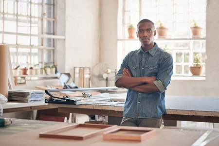 Photo pour Young man of African descent standing proudly with his arms folded in the workshop where he runs his small business from, looking at the camera seriously - image libre de droit