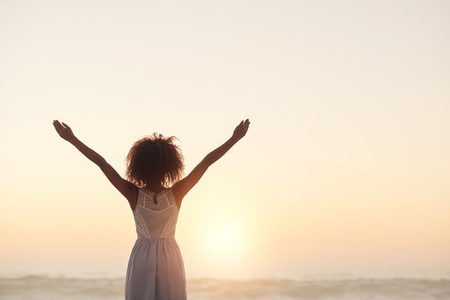 Photo pour Beautiful young woman standing on a beach with her arms raised in the air - image libre de droit