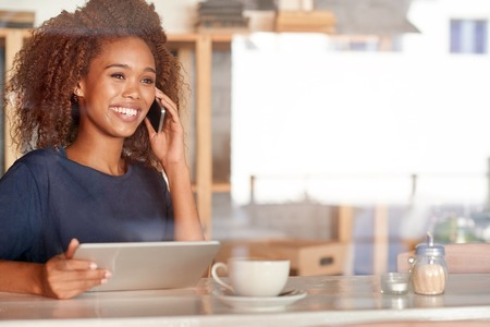 Photo pour Attractive young woman using a digital tablet and talking on the phone while sitting in a cafe - image libre de droit