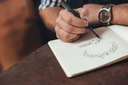 Foto de Closeup of a jeweler leaning on a bench sketching out new jewelry designs in a notebook while working in his shop - Imagen libre de derechos