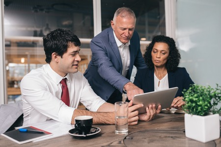 Photo pour Three diverse businesspeople talking together over a digital tablet while working at a table in an office boardroom - image libre de droit