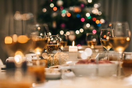 Dining table full of a variety of delicious festive food and wine with a Christmas tree in the background