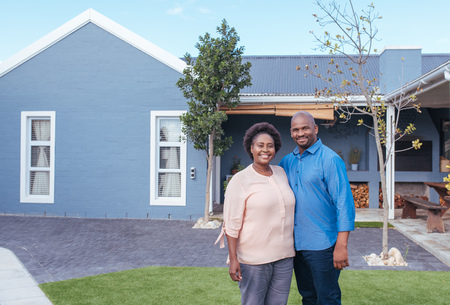 Photo pour Smiling African couple standing outside on their lawn - image libre de droit
