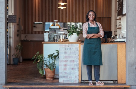 Photo pour Smiling African entrepreneur standing welcomingly in front of her cafe - image libre de droit