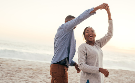 Foto de Laughing African couple dancing together on a beach at sunset - Imagen libre de derechos