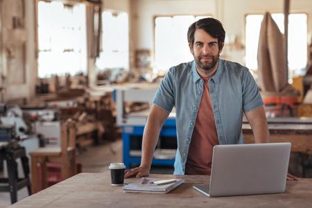 Photo pour Confident young craftsman using a laptop in his workshop - image libre de droit