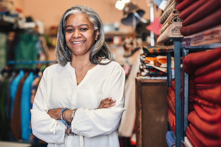 Smiling mature woman standing in her colorful fabric shop