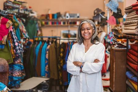 Foto de Mature woman smiling while standing in her fabric shop - Imagen libre de derechos