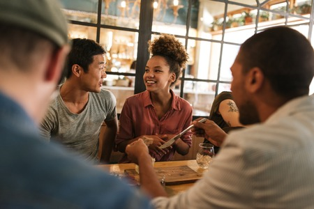 Photo for Smiling young friends talking together over a bistro dinner - Royalty Free Image