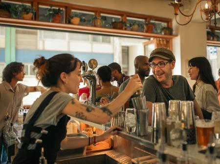 Photo pour Smiling patron ordering drinks in a trendy bar - image libre de droit