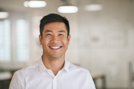 Foto de Young Asian businessman standing in an office smiling confidently - Imagen libre de derechos