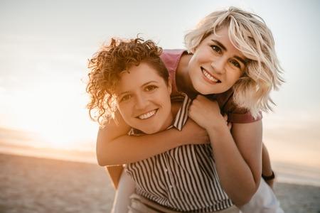 Photo pour Young woman giving her girlfriend a piggyback at the beach - image libre de droit