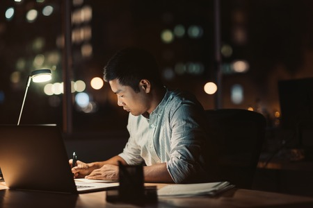 Photo for Asian businessman working at his desk late into the evening - Royalty Free Image