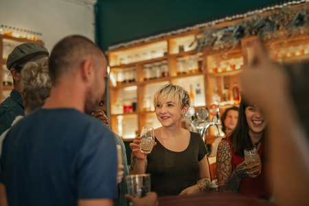 Photo pour Smiling group of friends having drinks together in a bar - image libre de droit