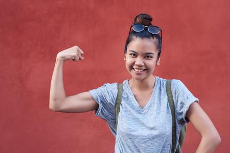 Foto de Young Asian woman smiling while humorously flexing her bicep outside - Imagen libre de derechos