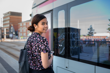 Photo pour Smiling young Asian businesswoman boarding a bus in the city - image libre de droit