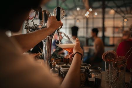 Foto de Bartender pouring beer behind a bar counter at night - Imagen libre de derechos
