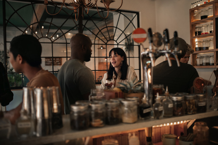 Foto de Diverse friends talking over drinks in a bar at night - Imagen libre de derechos