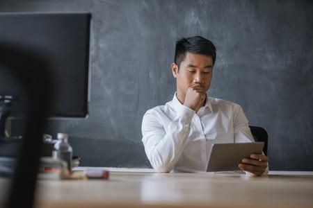 Foto de Asian businessman sitting at his desk working on a tablet - Imagen libre de derechos