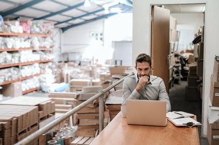 Foto de Manager working online while sitting in a warehouse office - Imagen libre de derechos