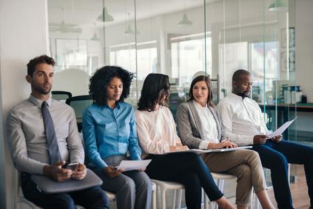 Photo pour Job applicants sitting in an office waiting for interviews - image libre de droit