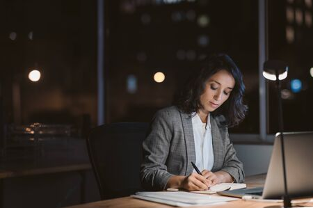 Photo pour Young businesswoman working in her office at night - image libre de droit