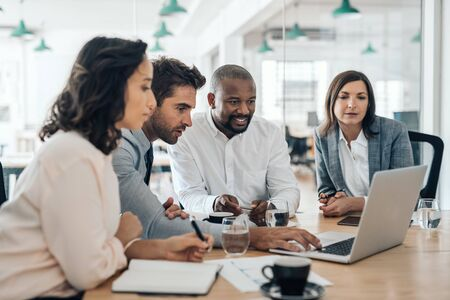 Photo pour Diverse businesspeople smiling while working together on a laptop - image libre de droit