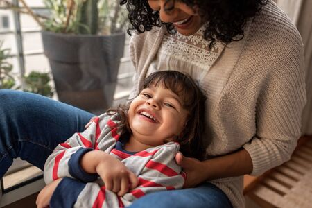 Photo for Smiling mother and adorable daughter playing together at home - Royalty Free Image