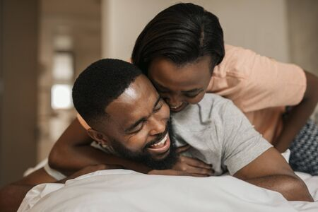 Photo for Laughing young African American couple playing in bed together - Royalty Free Image