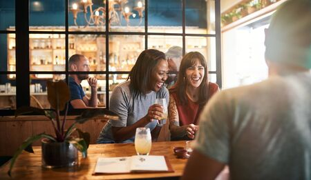 Photo for Diverse young friends laughing over drinks together in a bar - Royalty Free Image