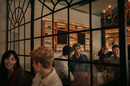 Photo for Young people talking over drinks at a bar at night - Royalty Free Image