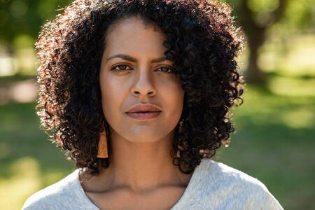 Photo pour Confident young woman standing in a park in summer - image libre de droit