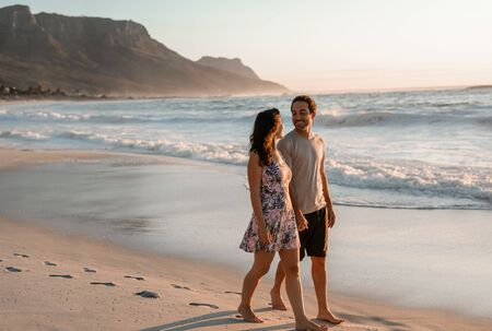 Photo for Loving young couple walking along a sandy beach - Royalty Free Image