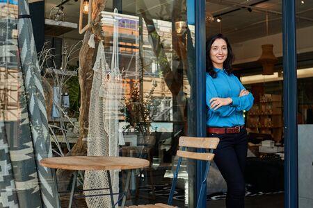 Photo pour Smiling Asian entrepreneur standing at the entrance of her boutique - image libre de droit