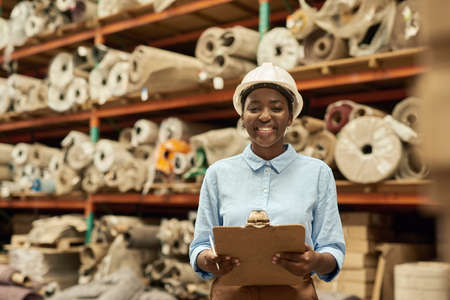 Photo pour Smiling African woman with a clipboard standing in a warehouse - image libre de droit