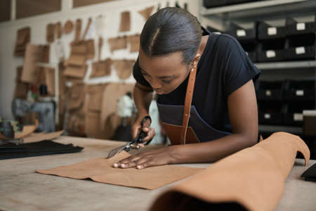 Photo pour Young African female artisan cutting leather in her workshop - image libre de droit