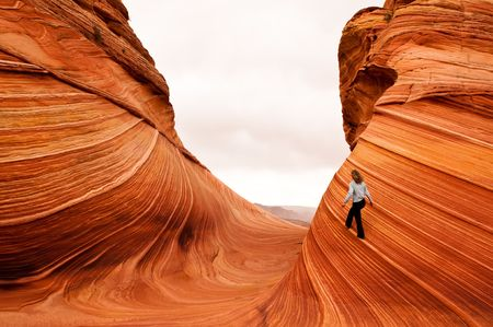 mature woman walking on vertical sandstone