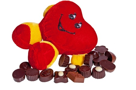 Plush heart in the midst of chocolates on a white background