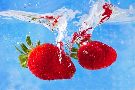 Fresh strawberries falling into the water on a blue mosaic backgroundの写真素材