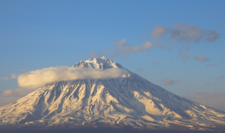 Volcano in a half ring of clouds. Are well visible barranco. Kamchatka
